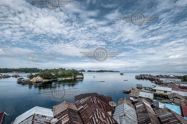 Boats travel through the Bajau stilt village of Kabalutan.