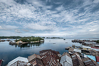 Boats travel through the Bajau stilt village of Kabalutan.