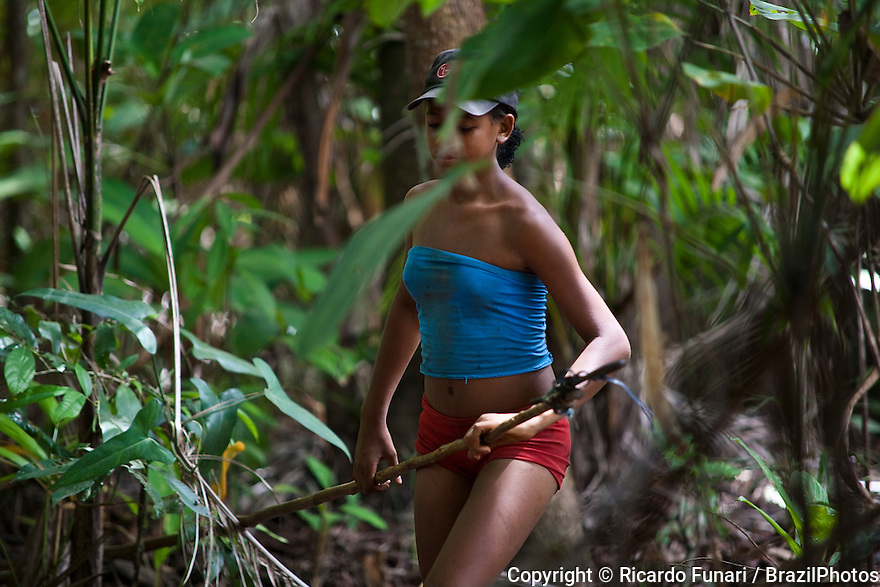 Teenager on her way to pick açaí fuits in the forests of São Raimundo Quilombo at Alcântara, Maranhão, Northeast Brazil. A quilombo is a Brazilian hinterland settlement founded by people of African origin. Most of the inhabitants of quilombos were escaped former slaves and, in some cases, a minority of marginalised non-slave Brazilians that faced oppression during colonization.