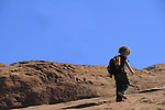 Young boy hiking uphill on slickrock in Arches National Park, Moab, Utah, USA. .  John offers private photo tours in Arches National Park and throughout Utah and Colorado. Year-round.