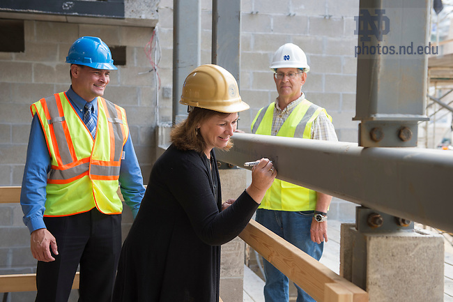 Sept. 3, 2015; Mary Hesburgh Flaherty signs a steel beam at the construction site of Flaherty Hall. (Photo by Barbara Johnston/University of Notre Dame)