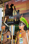 "Altamira, Brazil. ""Xingu Vivo Para Sempre"" protest meeting about the proposed Belo Monte hydroeletric dam and other dams on the Xingu river and its tributaries. Two kayapo cheifs infront of the poster ""Xingu alive forever""."