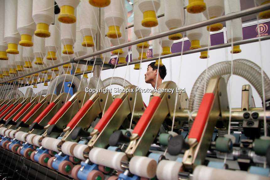 A visitor looking at textile machinery on display at the ShanghaiTex 2005, a textile industry exhibition in Shanghai, China. China is currently engaged in heated trade disputes with both the European Union and then United States over its exports of textiles to these two areas..05 Jun 2005
