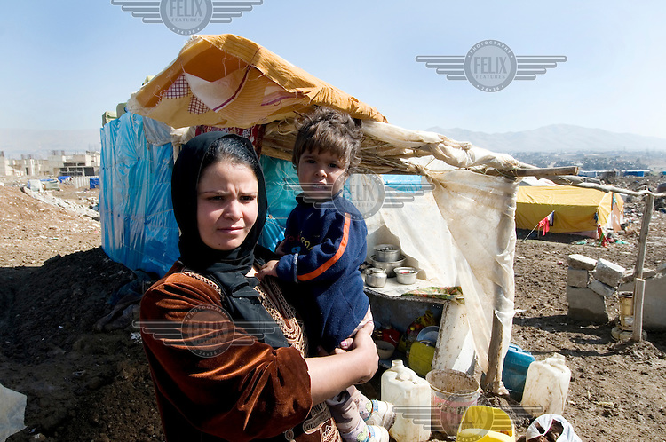 Ikhas Khalil Ibrahim is a widow and mother of two. She stands with one of her children in front of the tent that is home to her whole family, including her sister and parents, in the Qawala camp for displaced persons, where 136 families from accross the country are housed.