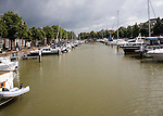 Boats at moorings in New Harbour, Nieuwe Haven, with passing rain clouds, Dordrecht, Netherlands