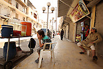 Fouad, a 11-year-old Syrian boy, sits next to his juice cart, in a street in a rebel-controlled area of Aleppo, on August 8, 2015. Fouad works everyday following the school time to provide for his small family, as his father suffers from disease. Children in the country were now contributing to the family income in more than three quarters of Syrian households, according the report released by UNICEF, estimates that one in ten Syrian refugee children in the region is engaged in child labour. Photo by Ameer al-Halbi