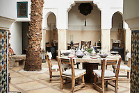 A round stone table is laid for an alfresco lunch on the courtyard patio. To one side is a covered terrace area with seating.