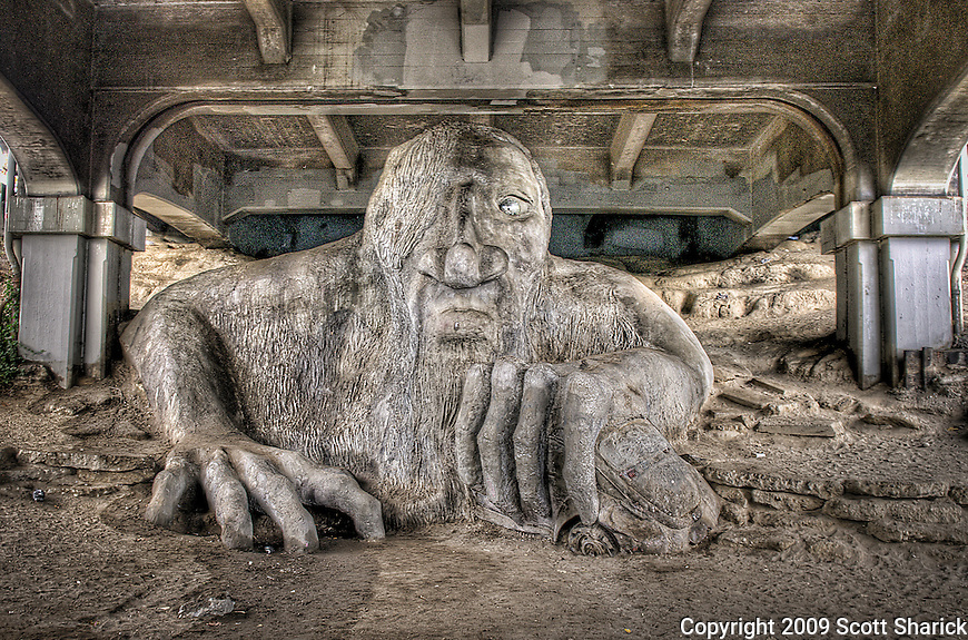 A full size VW Bug is held in the hand of a troll sculpture under a bridge in Seattle.