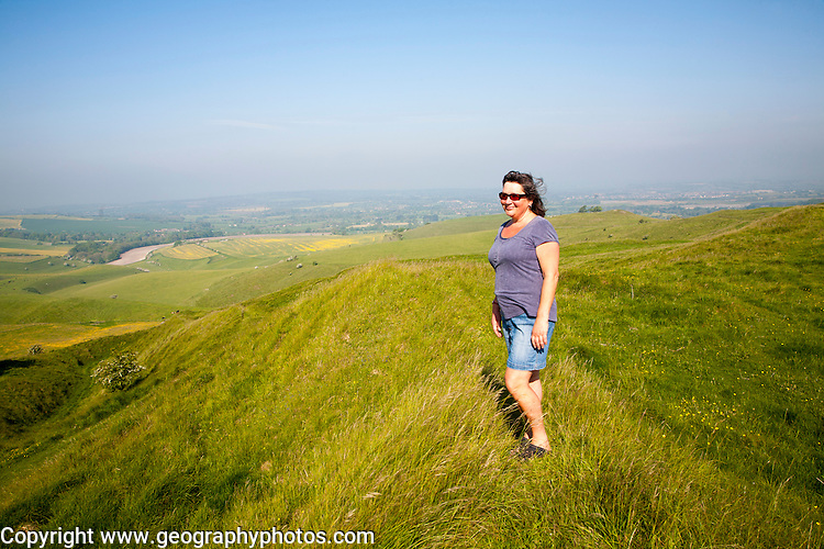 Woman standing on steep chalk scarp slope on downland at Cherhill Down, Wiltshire, England