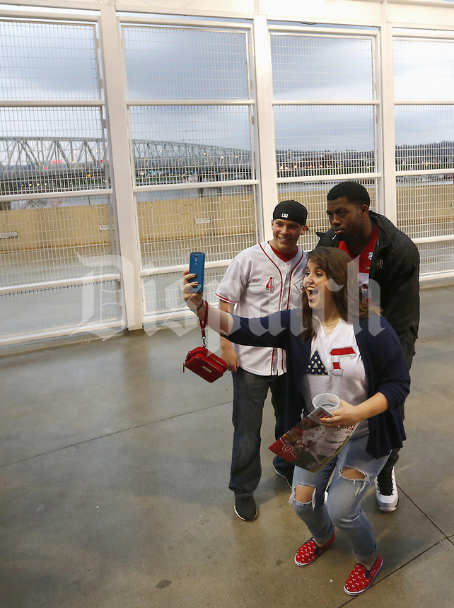 Ohio State quarterback J. T. Barrett poses with Mariah Tackett and fiancé Luke Fannin of Portsmouth as rain delays the start of the Reds/Pirates game at Great American Ball Park on Wednesday April 8, 2015. (Dispatch photo by Jonathan Quilter)