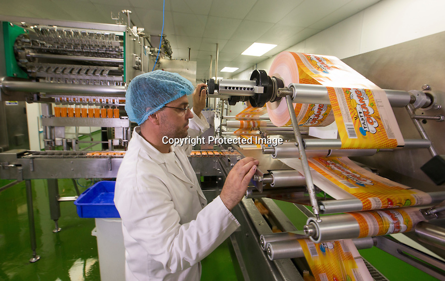 """19/06/16<br /> <br /> Francesco D'Errico, production manager, loads new wrappers.<br /> <br /> """"The last couple of days have sent the factory into meltdown,"""" exclaimed Pasquale Tanzarella, director of one of the UK's largest independent ice-lolly manufacturers.<br /> <br /> In fact, today alone, his factory will make more than 200,000 ice lollies, which will be sold up and down the country through traditional ice-cream vans and shops. <br /> <br /> Demand has been so high because of the recent hot spell that the cold rooms at Franco's ices, in Kempston, Bedfordshire, are already full to bursting, with more than 40 different varieties of ice-cream and ice-lollies, and today's production of Tasty Orange lollies will probably be on sale by late afternoon.<br /> <br /> The lollies start life in a huge 2,000-litre vat, as a syrupy, bright orange liquid, before being poured into the traditional ice-lolly moulds.<br /> <br /> From there they are passed over a fast-freezer, at around -36C, to super cool the liquid into ice, which only takes around 20 minutes, before being loaded into their colourful outer wrapper.<br /> <br /> And then it's straight into wholesale boxes, stored in the factory's cold rooms, and sold the very same day.<br /> <br /> It's a super success story for this family-run business, which was founded in1964 by Pasquale's father, Domenico Tanzarella, originally to sell ice-creams through a local chain of vans.<br /> <br /> """"In the 70s we used to only supply vans within about a 60-mile radius of the factory,"""" said Pasquale.<br /> <br /> """"But we've grown steadily over the years and now we export to Cyprus, Ireland and even South Africa, as well as being one of the biggest suppliers here in the UK.<br /> <br /> """"Our best seller by far is the Mr Bubble ice-lolly,"""" said Pasquale. """"We were the very first company to launch a bubble gum flavoured lolly and it's been our best seller ever since.""""<br /> <br /> Last year they sold more than five million of the bright"""