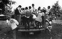 School children climb onto pick-up truck to take them home. Community of Nueva Esperanza, El Salvador, 1999.
