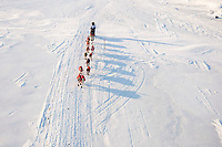Long shadows follow Paul Gebhart's team shortly after sunrise as he runs on the Unalakleet slough ice after leaving Unalakleet in Arctic Alaska during the 2010 Iditarod