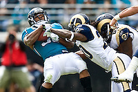 October 18, 2009:      Jacksonville Jaguars running back Maurice Jones-Drew (32) gets knocked backwards by St. Louis Rams cornerback Jonathan Wade (20) during action between the NFC West St. Louis Rams and AFC South Jacksonville Jaguars at Jacksonville Municipal Stadium in Jacksonville, Florida. Jacksonville defeated St. Louis in overtime 23-20............