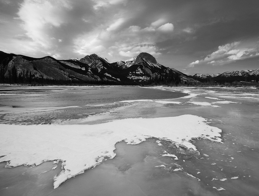 Clouds loom above the mountains in the background as seen from the shore of this frozen lake in Jasper National Park, Alberta, Canada.