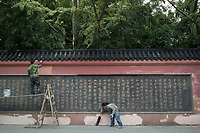 "Meishan, Sichuan province, China, October 2014 - Workers put finishing touches on an inscription of Su Dongpo's famous poem of the Battle of Chibi (Red Cliff) outside the Three Su Temple which was built to commemorate famous Song dynasty poet and politician Su and his father and brother who were also notable writers (the ""three Su""). Su Dongpo was native of Meishan."