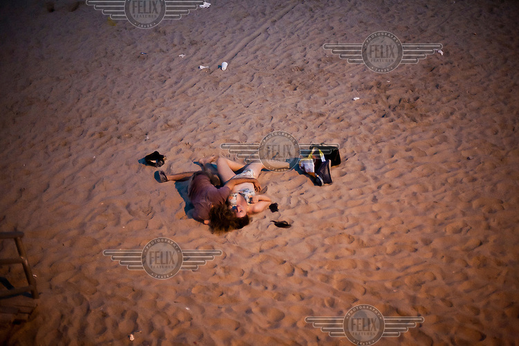 A couple lie together on the sand of Rockaway Beach in New York, long after most other people have left. Made famous by the classic song by The Ramones, it stretches for miles along the Atlantic Ocean, while still staying within the borders of New York City.