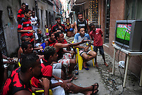 "Flamego fans watch soccer game on TV in a Favela da Mare alley, Rio de Janeiro, Brazil.  Flamengo is the most popular team in Brazil and one of the most popular teams in the world. Surveys show that there are over 33 million Flamengo supporters across Brazil. As such, Flamengo supporters are known as ""Nação Rubro-Negra"" (Scarlet-Black Nation), since there are more supporters of Flamengo than the population of many countries. Flamengo supporters are also known for their fanaticism. They hold several records in the Brazilian league like having the best average attendance, or the match with the greatest numbers of attendants between two football clubs."