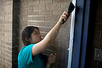 "Lina Ding scrapes paint off of a window in an entryway during ""Circle the City with Service,"" the Kiwanis Circle K International's 2015 Large Scale Service Project, on Wednesday, June 24, 2015, at the Friendship Westside Center for Excellence in Indianapolis. (Photo by James Brosher)"