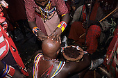 Lolgorian, Kenya. Siria Maasai; Eunoto ceremony; moran having his braided hair shaved off by a woman.