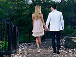 Young romantic couple walking through a park holding hands, rear view.
