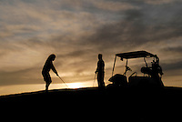 A couple golfing at sunset.