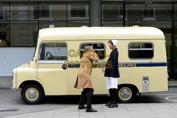Cast &amp; Crew<br /> Filming on the set of 'Breathless' in central London, England.<br /> 16th June 2013<br /> costume acting cast crew full length brown trench coat nurse hat white coat dress  cape ambulance <br /> CAP/IA<br /> &copy;Ian Allis/Capital Pictures