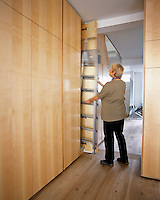 Architect Ann Grut takes out a ladder from a row of built-in cupboars in her contemporary London home