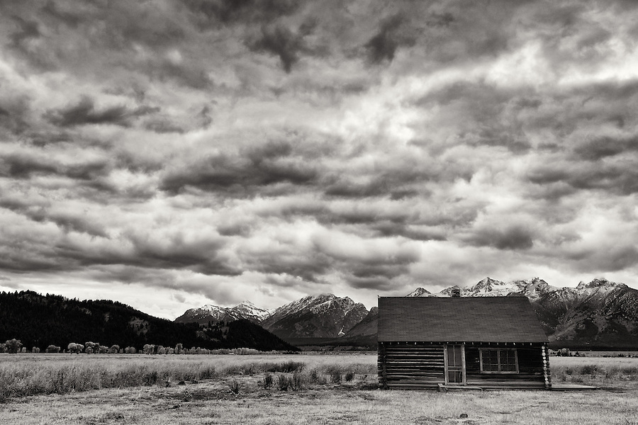 An old cabin sits alone while dramatic clouds fly overhead in Grand Teton National Park.