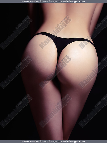 Sexy woman buttocks in black thongs isolated on black background, rear view