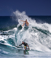 Surfer and bodyboarder sharing a wave at Sunset Beach on North Shore of Oahu.