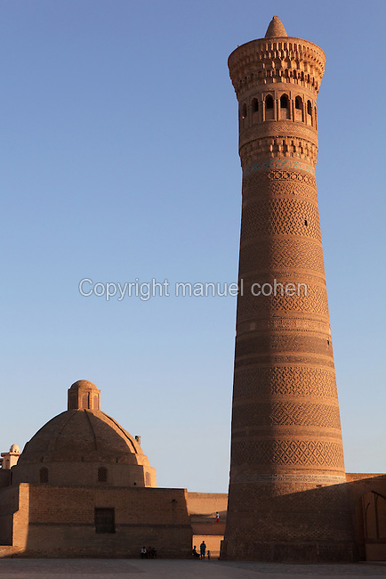 Low angle view of Kalyan Minaret, 1127,  and Amir Alim-Khan Madrasah, 14th century, Bukhara, Uzbekistan, pictured on July 8, 2010 in the afternoon. The baked brick  minaret is 48 metres high and its diametre is 9 metres at the bottom and 6 metres at the top. Commissioned by Arslan Khan and designed by Bako its purpose was to summon Muslims to prayer. Bukhara, a city on the Silk Route is about 2500 years old. Its long history is displayed both through the impressive monuments and the overall town planning and architecture. Picture by Manuel Cohen.