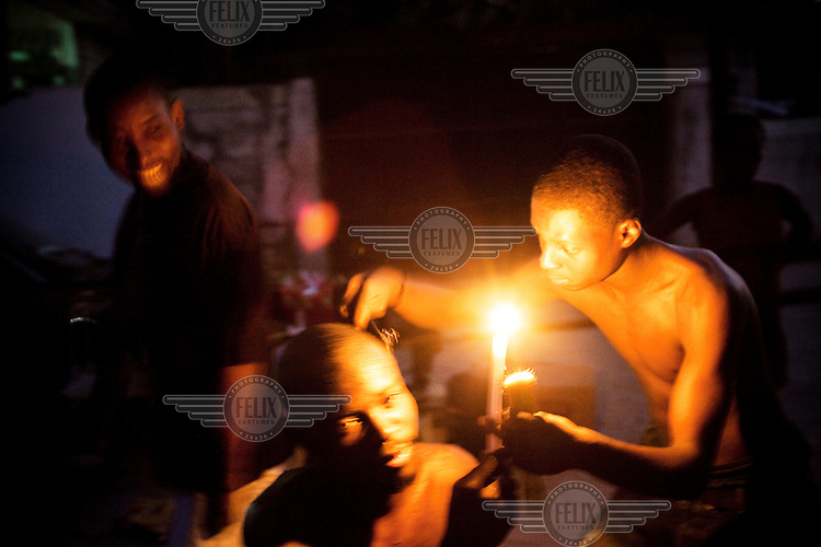 A young man shaves his friend's head by candlelight in the Fontamara area of the city. They were made homeless when a 7.0 magnitude earthquake struck Haiti on 12/01/2010. Early reports indicated that more than 100,000 may have been killed and three million affected.