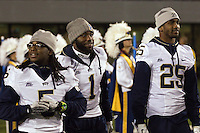 Injured Panther players Cam Saddler (5), Ray Graham (1) and Jason Hendricks (25) walk out to the sidelines. The WVU Mountaineers beat the Pitt Panthers 21-20 at Mountaineer Field in Morgantown, West Virginia on November 25, 2011.