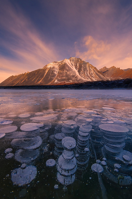 An interesting array of methane gas bubbles trapped in a frozen lake, complemented by a colorful sky and reflected peaks in Yukon's Ogilvie Mountains.