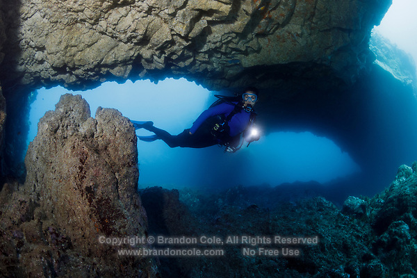 WQ1889-D. Scuba diver (model released) swims through a caver with three arched openings. The volcanic islands of the Azores archipelago off mainland Portugal have many swim throughs, caves, and lava tunnels awaiting exploration by the adventurous diver. Azores, Portugal, Atlantic Ocean.<br /> Photo Copyright © Brandon Cole. All rights reserved worldwide.  www.brandoncole.com
