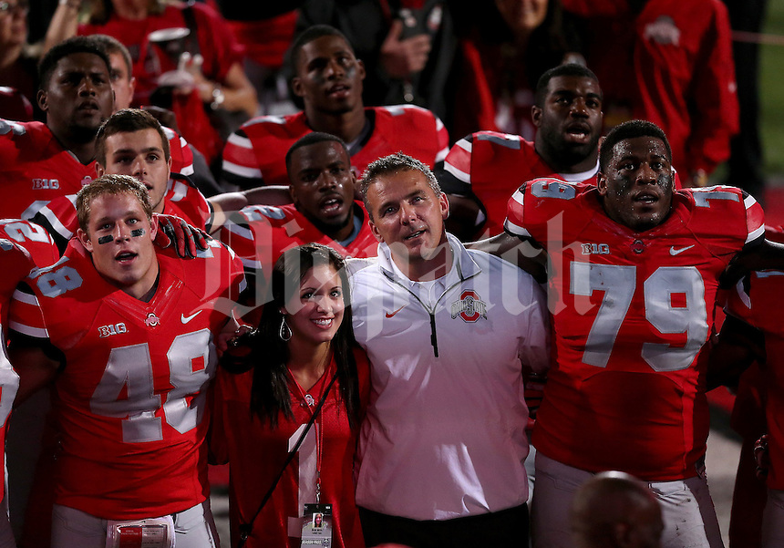 Ohio State Buckeyes head coach Urban Meyer sings Carmen Ohio with his daughter Nicole Meyer during the fourth quarter of the game between Ohio State and Wisconsin at Ohio Stadium on Saturday, September 28, 2013. At left is Ohio State Buckeyes linebacker Joe Burger (48) and right is Ohio State Buckeyes offensive linesman Marcus Hall (79). (Columbus Dispatch photo by Jonathan Quilter)