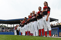 Batavia Muckdogs players including Hayden Fox, Jacob Smigelski, Ryan Cranmer, James Buckelew, John Norwood, Carlos Duran, Iramis Olivencia, Chris Hoo and Kevin Grove stand for the national anthem before a game against the Brooklyn Cyclones on August 11, 2014 at Dwyer Stadium in Batavia, New York.  Batavia defeated Brooklyn 4-3.  (Mike Janes/Four Seam Images)