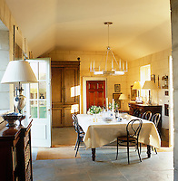 Sun pours into the dining room from the windows and door which line the faux stone walls.