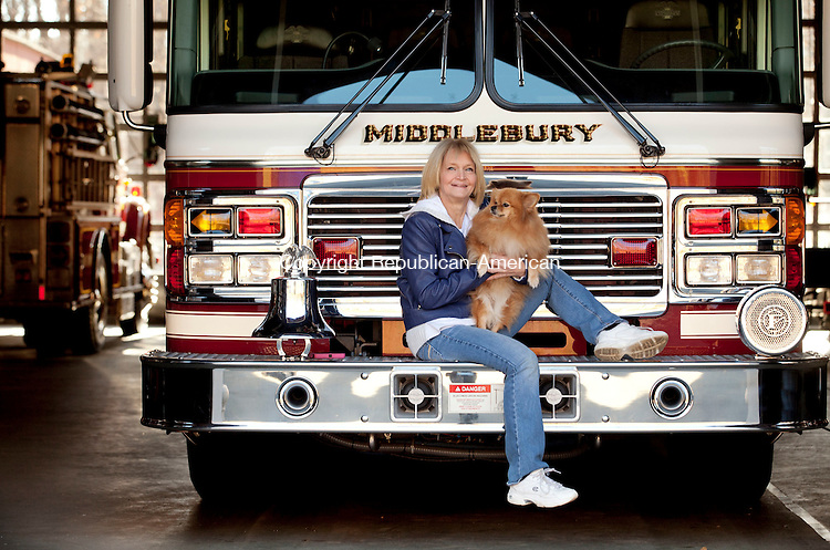 MIDDLEBURY, CT-14 November 2013-111413BF03- Beverly Dassonville poses with her 5-year old Pomeranian Chloe on a Middlebury Fire Department truck Thursday morning. Dassonville is a volunteer E.M.T. with the Middlebury Fire Department Ambulance and created a video that she entered to try to win a $500,000 dog park from the the pet food company Beneful in the Beneful Dream Dog Park Contest.  Bob Falcetti Republican-American