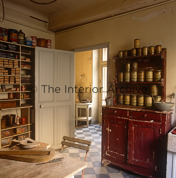 A rustic kitchen with a distressed plaster finish on the walls and a blue and white tiled floor. Storage jars are arranged on the shelves of a red painted dresser and tins and boxes are arranged on shelves.