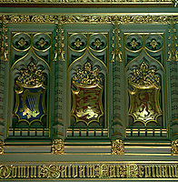 Decorative heraldry in moulded niches is gilded and painted with flower motifs