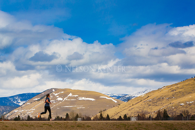 A jogger on an early spring day in Missoula, Montana with Mount Jumbo in the background.