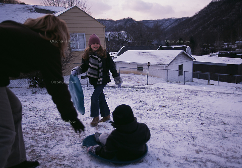 A family takes advantage of a morning snow when schools were called off for the day and the children could sled.