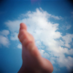 Child's foot in air against blue sky with clouds