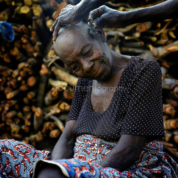 Kobepaa Matinga Tongo is getting her hair cut by resident of the camp.