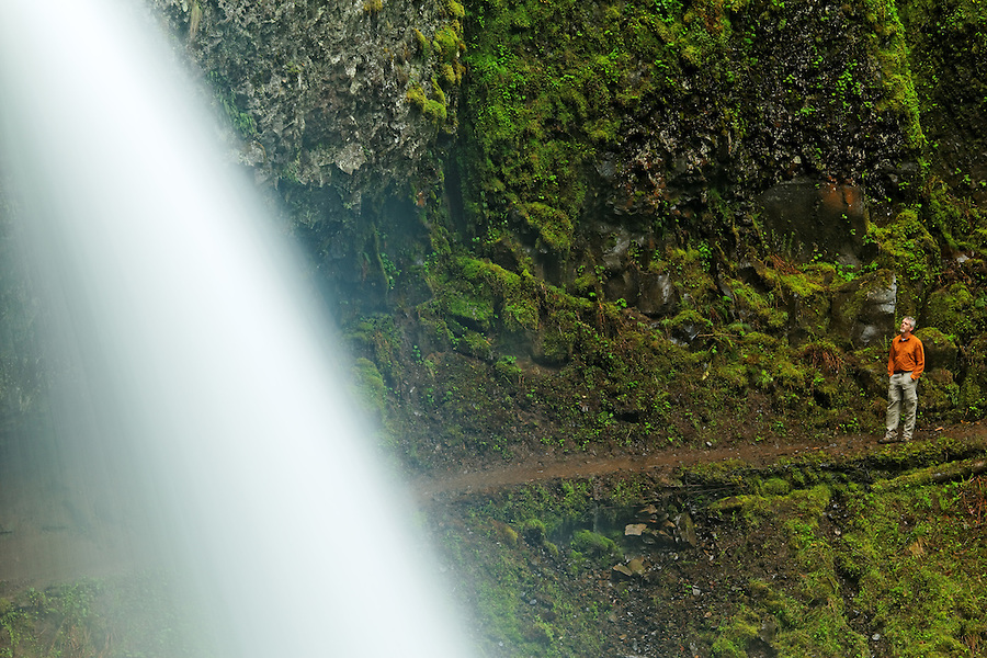 Man on trail behind Ponytail Falls and moss covered boulders, Columbia River Gorge National Scenic Area, Oregon, USA