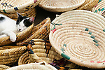 Blissfully unaware of passers-by, a cat sleeps in baskets for sale at a market in Morocco.
