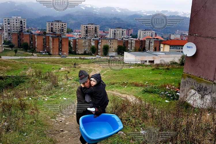 A woman carries her child and a plastic baby bath on the outskirts of Vulcan.