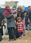 Displaced by fighting between the Iraqi army and the Islamic State group, a family leaves a processing center for displaced families outside Mosul, Iraq, on January 27, 2017. Although the eastern portion of the city has been liberated from ISIS, fierce fighting is predicted as the army moves to retake the remainder of the city.
